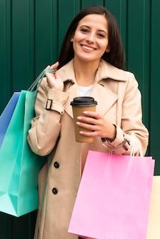 Vista frontal de la mujer sonriente sosteniendo bolsas y taza de café
