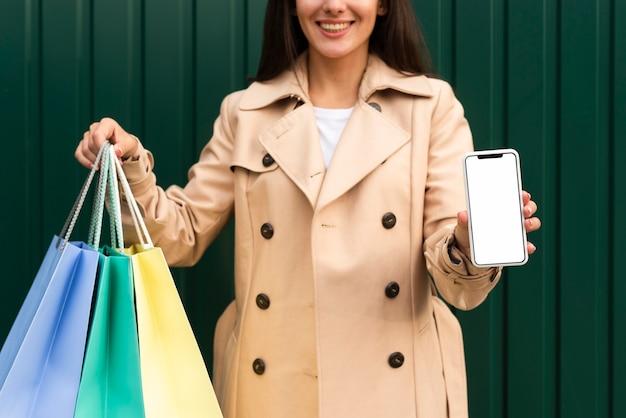 Vista frontal de la mujer sonriente sosteniendo un teléfono inteligente y bolsas de la compra.
