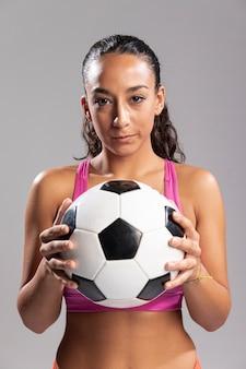Vista frontal mujer sosteniendo el balón de fútbol