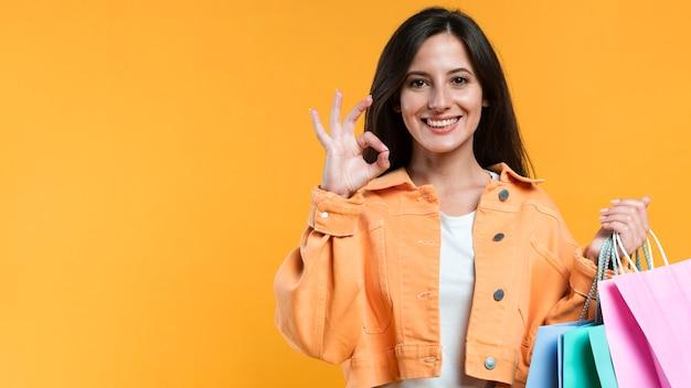 Vista frontal de la mujer sosteniendo bolsas de la compra y haciendo el signo de ok