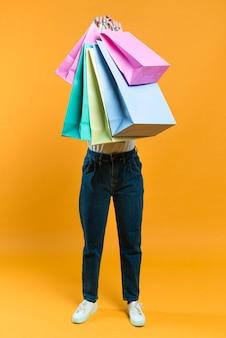 Vista frontal de la mujer sosteniendo bolsas de compra venta