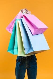 Vista frontal de la mujer sosteniendo bolsas de la compra.