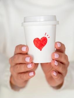 Vista frontal mujer sosteniendo café de san valentín
