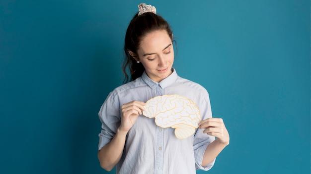 Vista frontal mujer sosteniendo cerebro de papel