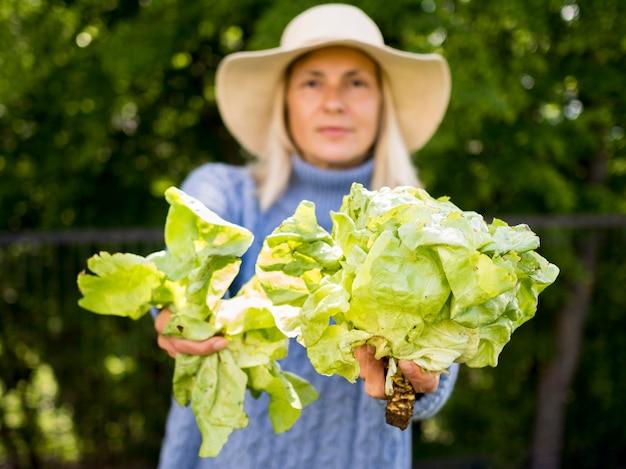 Vista frontal mujer sosteniendo una col verde