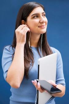 Vista frontal de la mujer sosteniendo la computadora portátil y escuchando música en los auriculares