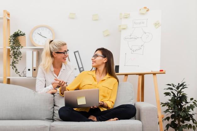 Vista frontal mujer sosteniendo una computadora portátil y mirando a su colega