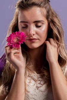 Vista frontal de la mujer sosteniendo un crisantemo cerca de su cara