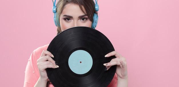 Vista frontal de la mujer sosteniendo un disco de vinilo mientras usa auriculares