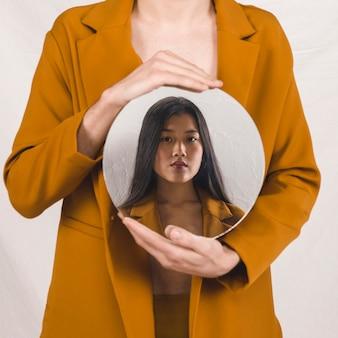 Vista frontal de una mujer sosteniendo un espejo redondo con su cara.