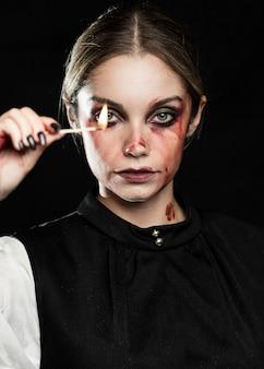 Vista frontal de la mujer sosteniendo fósforo encendido