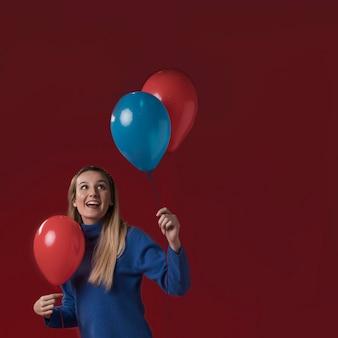 Vista frontal mujer sosteniendo globos