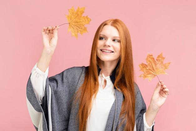 Vista frontal mujer sosteniendo hojas