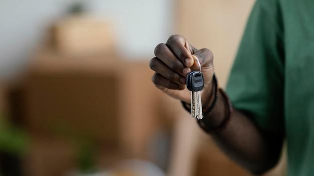 Vista frontal de la mujer sosteniendo las llaves de su nueva casa