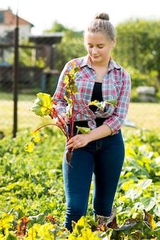 Vista frontal mujer sosteniendo planta