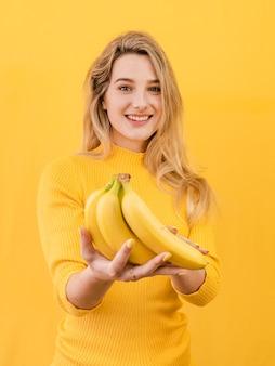 Vista frontal mujer sosteniendo plátanos