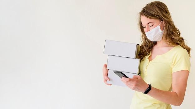 Vista frontal mujer sosteniendo productos comprados en línea