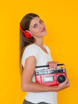 Vista frontal de la mujer sosteniendo una radio