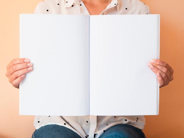 Vista frontal mujer sosteniendo una revista de maquetas