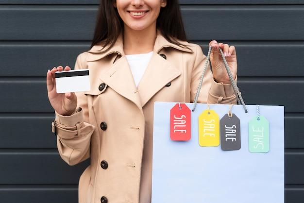 Vista frontal de la mujer sosteniendo una tarjeta de crédito y una bolsa de compras con etiquetas de venta