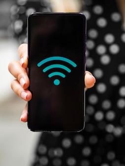 Vista frontal mujer sosteniendo teléfono con símbolo wifi en pantalla