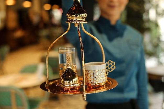 Vista frontal mujer sostiene una bandeja con café turco y delicias turcas con un vaso de agua.
