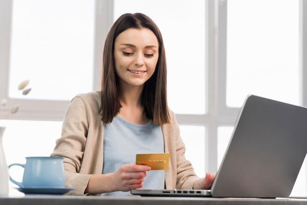 Vista frontal de la mujer con tarjeta de crédito y trabajando en la computadora portátil