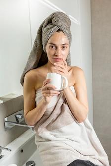Vista frontal mujer con toalla en el baño