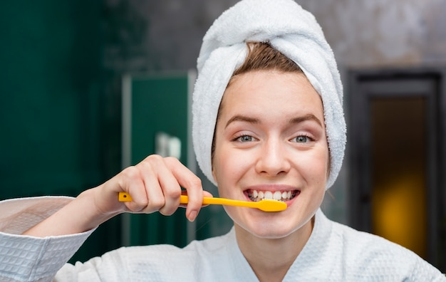 Vista frontal de la mujer con una toalla cepillando sus dientes