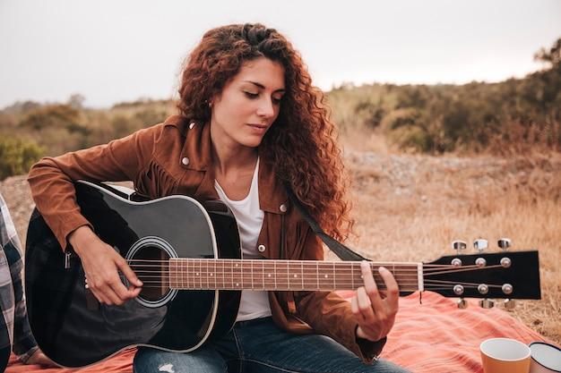 Vista frontal mujer tocando la guitarra