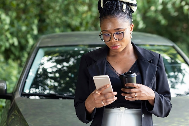 Vista frontal de la mujer tomando café y mirando el teléfono inteligente mientras se inclina contra su coche