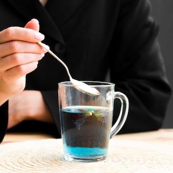 Vista frontal mujer tomando cucharadita de taza de té