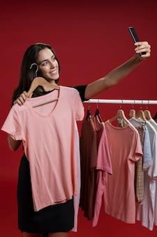 Vista frontal mujer tomando un selfie con una camiseta rosa