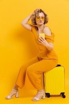 Vista frontal de la mujer tomando una selfie mientras está sentado en el equipaje