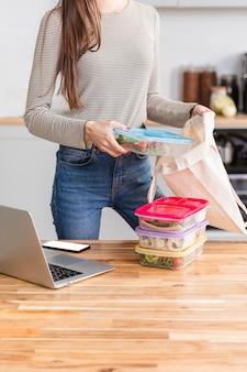 Vista frontal mujer trabajando desde casa y comida