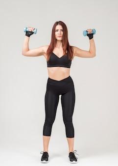 Vista frontal de la mujer en traje de gimnasio haciendo ejercicios con pesas