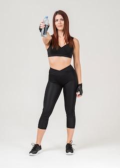 Vista frontal de la mujer en traje de gimnasio posando mientras sostiene una botella de agua