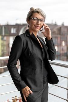 Vista frontal mujer en traje hablando por teléfono