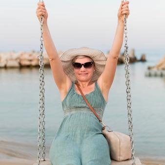 Vista frontal de la mujer turista senior con gafas de sol en el columpio de playa