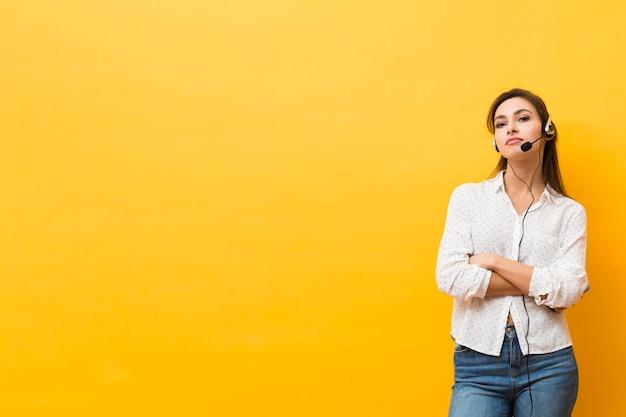Vista frontal de la mujer usando auriculares posando con los brazos cruzados