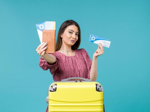 Vista frontal mujer en vacaciones sosteniendo sus boletos en el escritorio azul viaje mar mujer viaje vacaciones verano