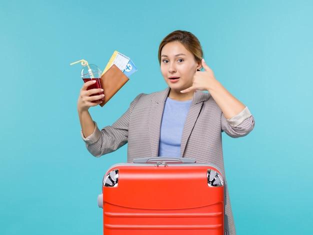 Vista frontal mujer en vacaciones sosteniendo un vaso de jugo fresco y boletos en el escritorio azul viaje en avión viaje de vacaciones en el mar