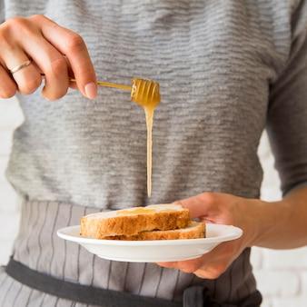 Vista frontal mujer vertiendo miel ober rebanada de pan