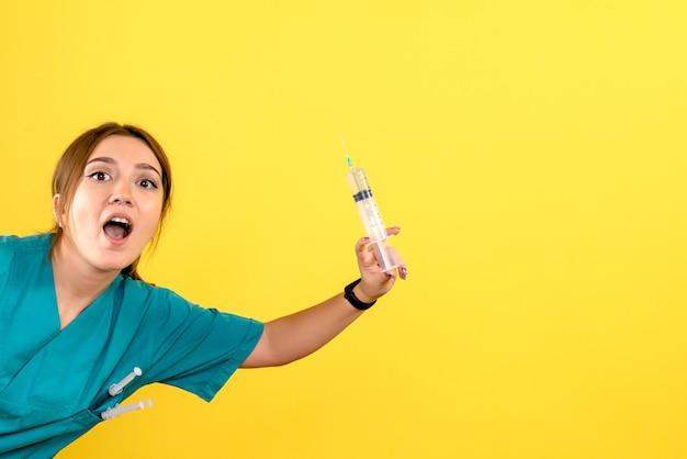 Vista frontal de la mujer veterinaria sosteniendo una inyección enorme en la pared amarilla