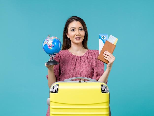 Vista frontal mujer en viaje sosteniendo boletos y globo sobre fondo azul mujer viaje vacaciones viaje por mar viaje