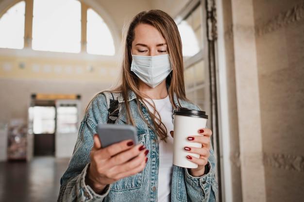 Vista frontal mujer vistiendo máscara médica en la estación de tren