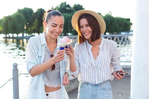 Vista frontal de las mujeres brindando con sus helados.