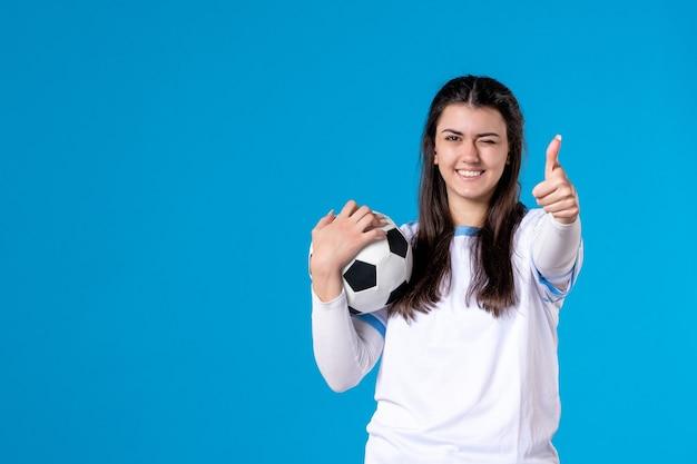 Vista frontal de las mujeres jóvenes con balón de fútbol en la pared azul