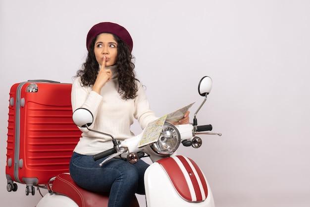 Vista frontal de las mujeres jóvenes en bicicleta sosteniendo el mapa pensando sobre fondo blanco, carretera de vuelo, motocicleta, vehículo de vacaciones, ciudad, velocidad, color