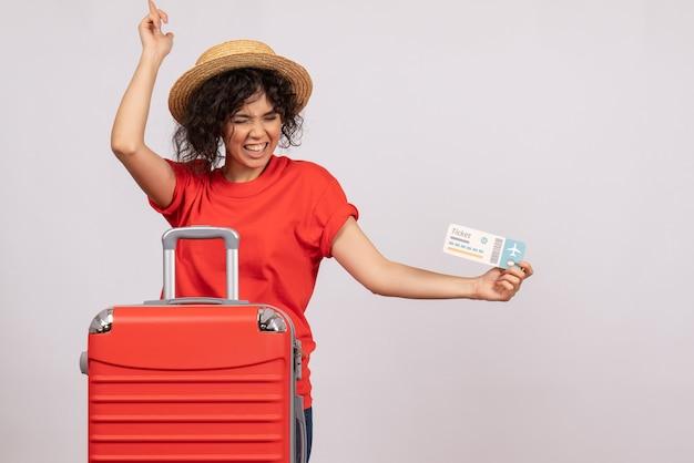 Vista frontal de las mujeres jóvenes con bolsa preparándose para el viaje sosteniendo el boleto sobre fondo blanco, color, sol, viaje, vacaciones turísticas, descanso, vuelo, avión